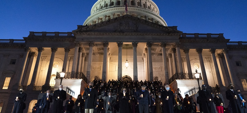 Members of Congress hold a moment of silence for 500,000 U.S. COVID-19 deaths, Tuesday, Feb. 23, 2021, on the east front steps of the Capitol in Washington.