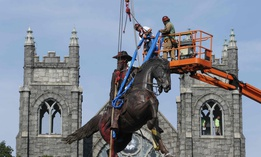 Crews attach straps to the statue Confederate General J.E.B. Stuart on Monument Avenue in Richmond, Va.