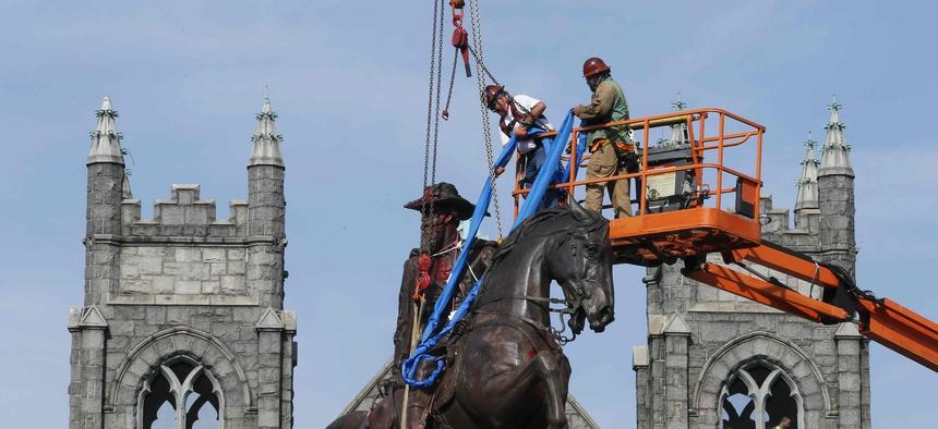 Crews attach straps to the statue Confederate General J.E.B. Stuart on Monument Avenue in Richmond, Va.