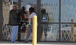 People are unable to enter a business closed due to the coronavirus outbreak Thursday, May 7, 2020, in St. Louis.