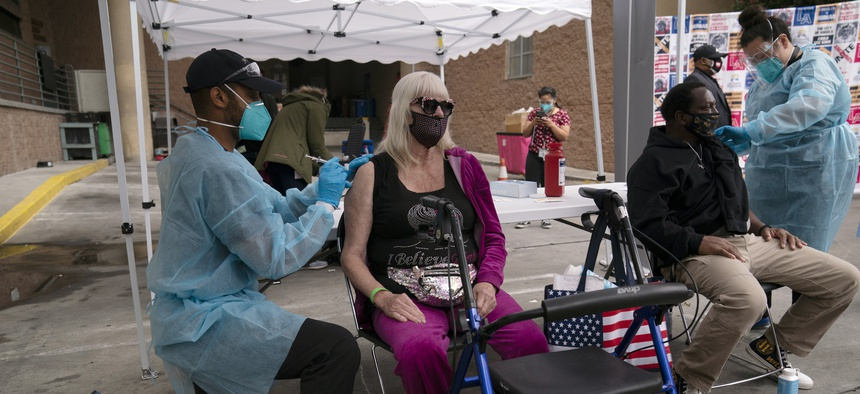 A nurse administers a COVID-19 vaccine to Connie Lach, 66, at a vaccination site set up in the parking lot of the Los Angeles Mission in the Skid Row area of Los Angeles, Wednesday, Feb. 10, 2021.