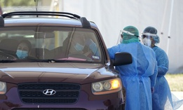 Medical personnel administer COVID-19 testing at a drive-thru site in San Antonio.